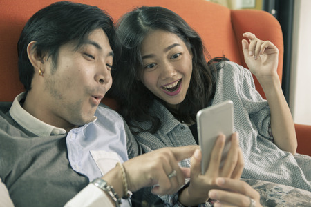 asian younger man and woman watching on smart phone with surprising and happiness  face,internet and social media concept