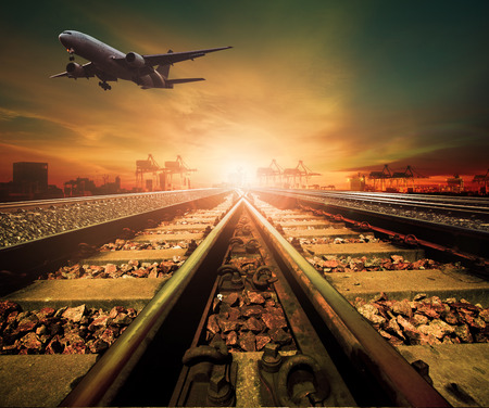 railway transportation: track of railway and cargo plane flying above logistic ship port background for transportation business
