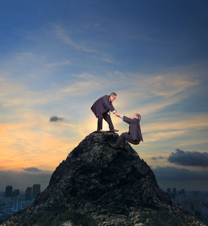 two of asian business man helping hand to climbing up to peak of rock mountain abstract of team work and partner for successful business