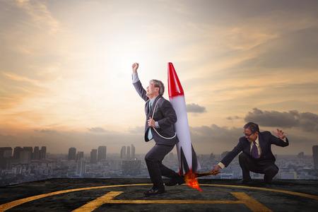 twee business man spelen raket speelgoed op hoog gebouw dak met wolkenkrabber achtergrond voor een succesvolle zakelijke partner Stockfoto
