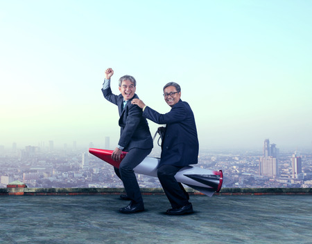 two asian business man funny playing with rocket missile on building roof happiness emotion