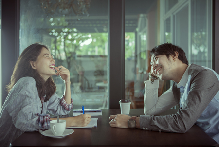 couples of younger asian man and woman relaxing with hot coffee drink in coffee shop happiness feeling Foto de archivo