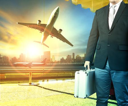 business man and breifcase standing in airport terminal building and passenger plane arrival on runway Stock Photo