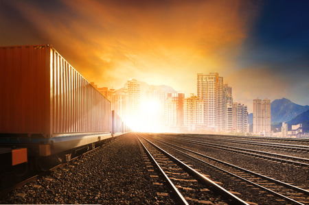 industry container trainst running on railways track against beautiful sun set sky use for land transport and logistic business  Stock Photo