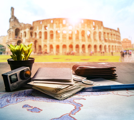 bank note: passport euro money bank note and action camera on wood table against colosseum scene background for rome italy traveling theme
