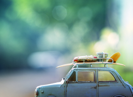 summer holiday: old classic retro car with surf board and beach  tool on roof against beautiful blur background for vacation traveling theme