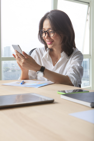 office life: office table scene of asian working woman reading message on mobile phone for modern life connecting Stock Photo