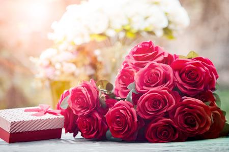 Flores de rosas rojas con el regalo del festival de San Valentín y el fondo hermoso ramo de desenfoque Foto de archivo