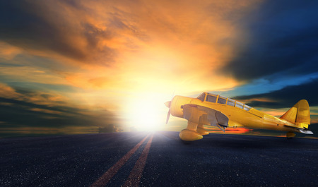 old yellow propeller plane on airport runway with sunset sky background