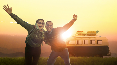 younger man and woman happiness emotion traveling to destination against beautiful sun set sky  Stock Photo