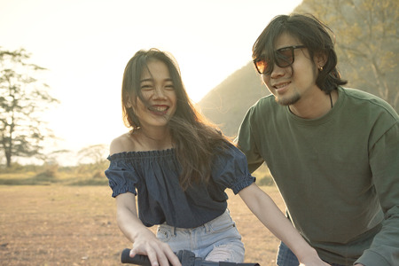 hobbies: couples of younger asian man and woman practice to riding bicycle in natural field relaxing emotion