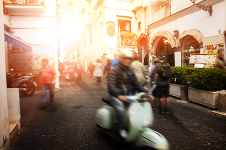 sorrento: man riding scooter motorcycle in amalfi street south italy most popular traveling destination Stock Photo