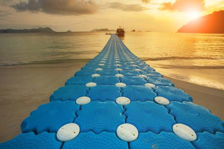 path of floating pier on sea beach against beautiful sun rising sky