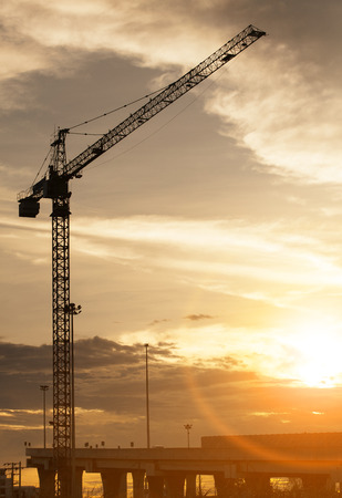 infra construction: crane at construction site and sunset sky