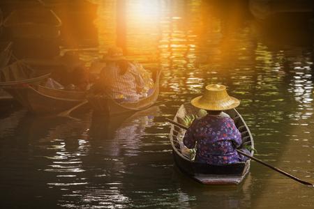 woman sailing thai trading boat in floating maket most popular traveling destination in dumnern sadauk canal ratchaburi thailand