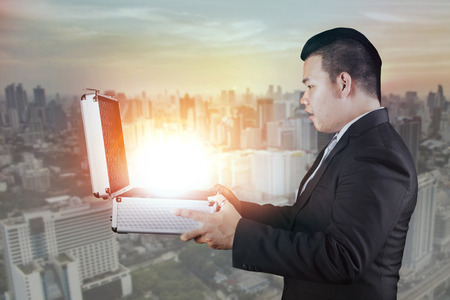 goodluck: asian business man open business briefcase with surprising face against residential building background Stock Photo