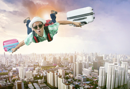 happiness face of asian traveling man flying with two luggage bag floating mid air over town skyscraper Zdjęcie Seryjne - 80151041