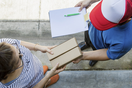 woman accepting on line shopping product from home delivery man ,top view scene