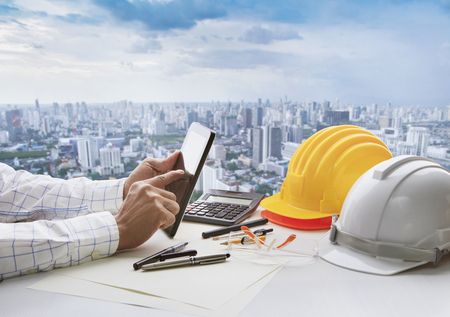 hand of business man touching on computer tablet screen and safety helmet on working table against cities of high building background Stock Photo
