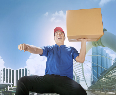 delivery man carrying card box with haapiness emotion in city building ,for delivering and courier business Stock Photo