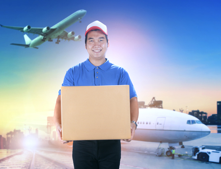 delivery man holding card box toothy smiling face against shipping port and cargo plane flying background