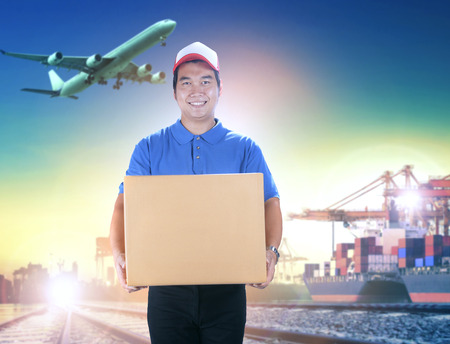 delivery man holding card box toothy smiling face against shipping port and cargo plane flying background Banco de Imagens - 80192755