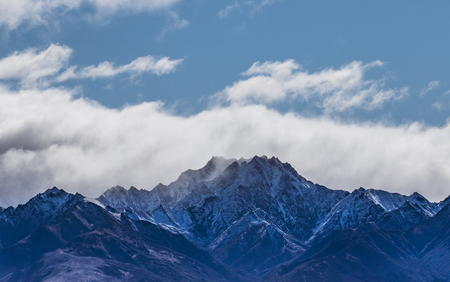 blue sky white cloud and peak of snowcapped mountain at lake wanaka new zealand Stock Photo