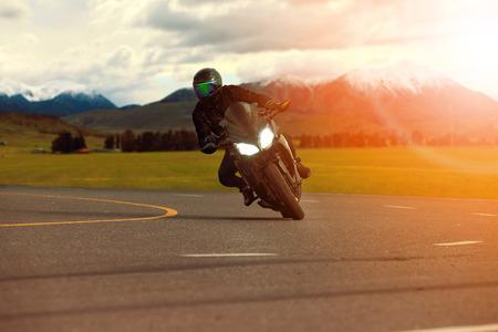 Man rijden sportmotor leunend in scherpe bocht met reizende scène achtergrond