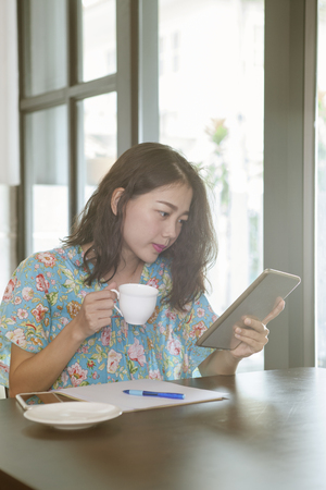 asian younger woman reading news from social media and other hand holding hot coffee cup in home living room Stock Photo