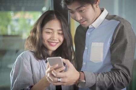 Aziatische jongere man en vrouw op zoek naar slimme telefoon scherm toothy lachend gezicht geluk emotie Stockfoto
