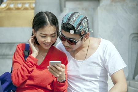 Koppels van Aziatische jongere man en vrouw op zoek naar slimme telefoon in reizende bestemming