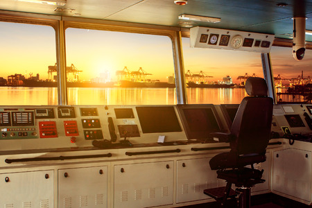 wheelhouse control board of modern industry ship approaching to harbor at night Reklamní fotografie