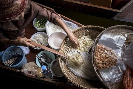oude vrouw die Thais noedelvoedsel maakt door in lokale drijvende bootmarkt te varen Stockfoto