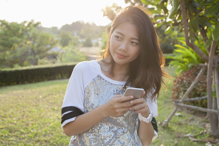 asian younger woman with smartphone in hand happiness thinking ,relaxing outdoor