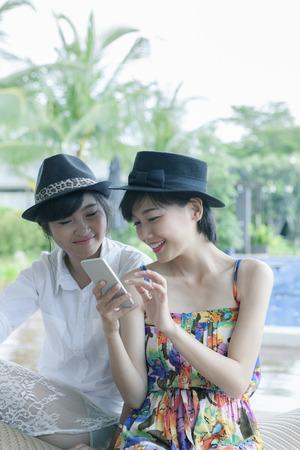 Mooie Aziatische jongere vrouw toothy glimlachende gezicht en spelen op slimme telefoon scherm