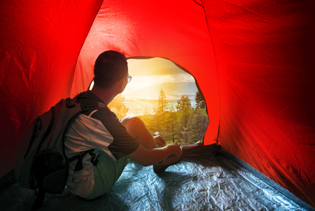 camping man in outdoor tent looking to beautiful sun rise scene photo