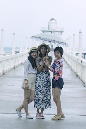 Drie jongere Aziatische vrouwvriend onder een paraplu in het regenseizoen Stockfoto