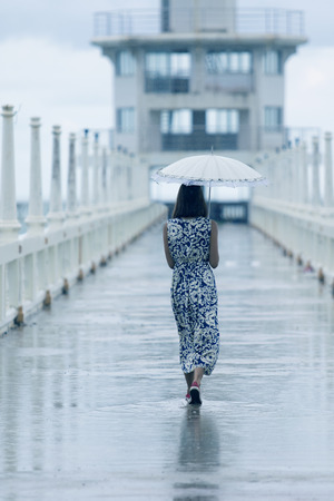single woman walking on way with umbrella and rain dropping Stock Photo