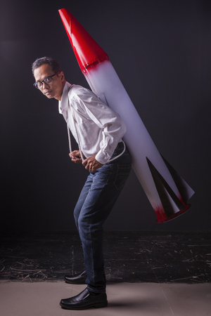asian man carrying  red head missile on back photo