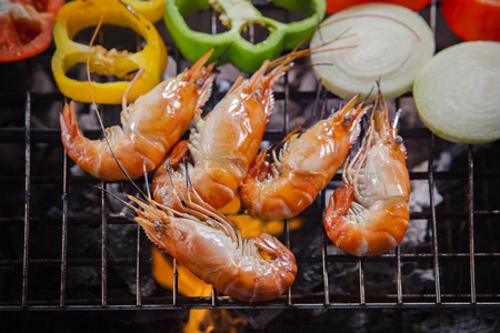 thai fresh water shrimp grilled on barbecue fire stove with chilly and onion ring
