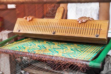 古いアジアの女性の家庭生活の自然なたたみを作るためタイ国内ツールの背後に働く