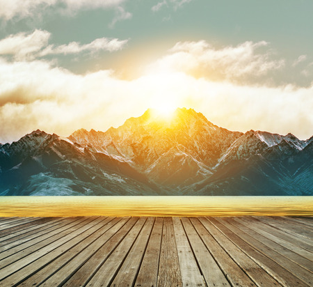 wood terrace and fresh water lake with sun rising behind snowcaped mountain Stock Photo