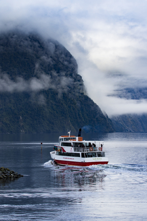 anau: MILFORD SOUND NEW ZEALAND - AUGUST 30,2015 : tourist boat cruising in harbor of milford sound most popular natural traveling destination in southland new zealand