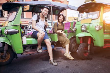 couples of young traveling people sitting on tuk tuk bangkok thailand 写真素材