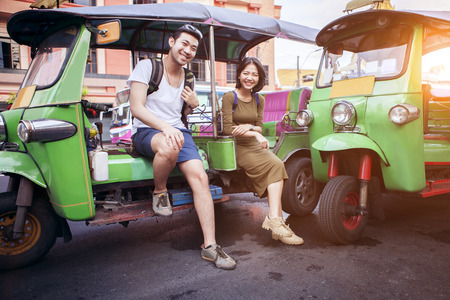couples of young traveling people sitting on tuk tuk bangkok thailand Standard-Bild