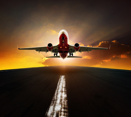 passenger plane take off from airport runway agasint beautiful sun rising sky Imagens