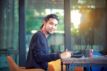 Aziatische freelance man aan het werk op computer laptop toothy lachend gezicht