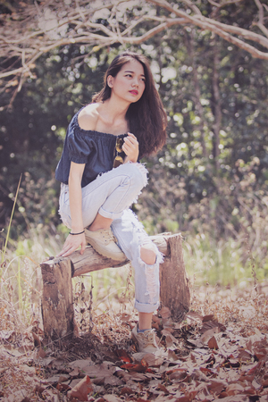 younger asian fashion model woman pose for photography in dry leaves forest