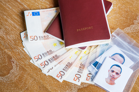 red cover passport book ,face of asian man with fifty euro bank note on wood table