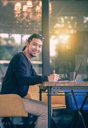 asian younger freelance man working at home office  with computer laptop toothy smiling face